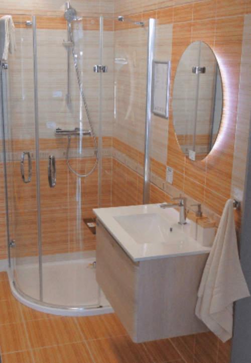 Osvětlené kulaté zrcadlo nad umyvadlo
